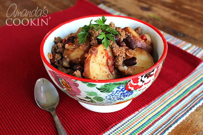 A multicolored bowl filled with cowboy casserole and a spoon on the side.
