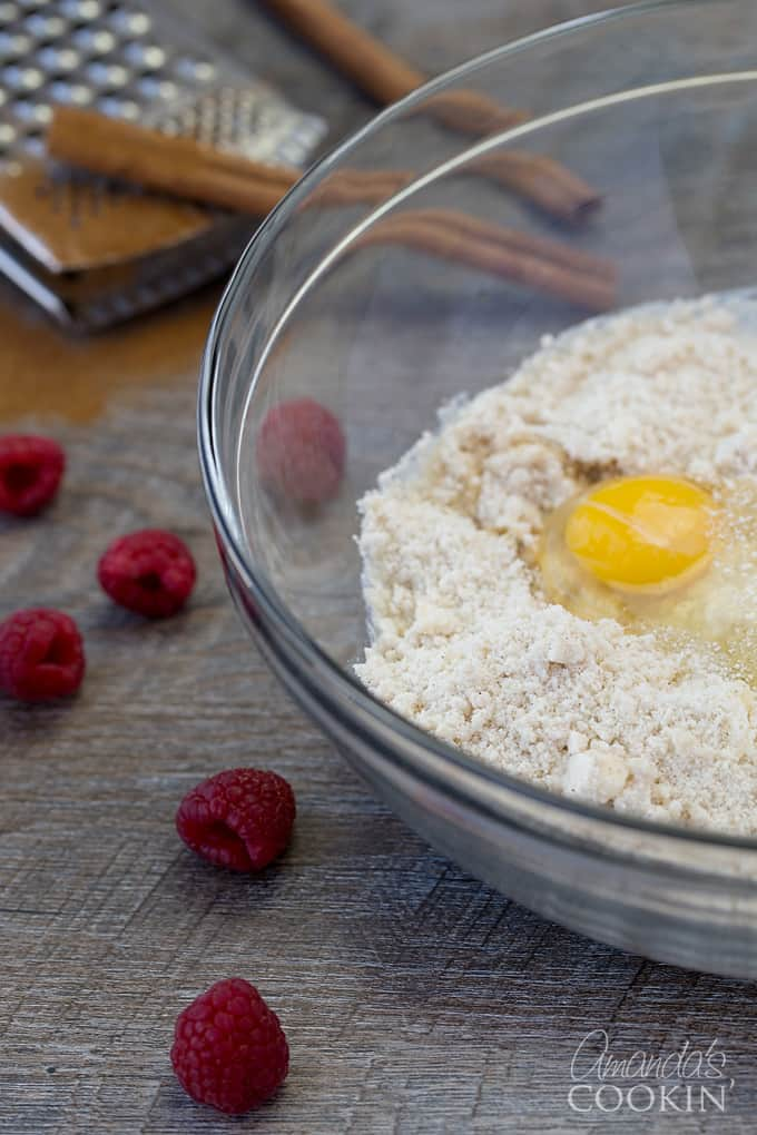Raspberries and a clear bowl resting on table. The clear bowl is filled with a flour mixture and a freshly cracked egg yolk.