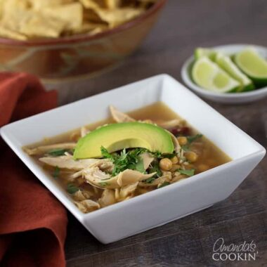 A square white bowl filled with chipotle chicken soup, topped with sliced avocado.