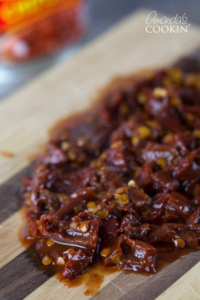 A close up of chopped chipotle chili peppers on a wooden cutting board.