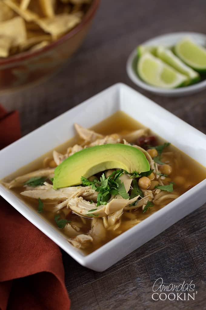 A close up of a square white bowl filled with chipotle chicken soup, topped with one slice of avocado.