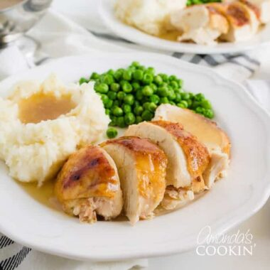 sliced chicken with mashed potatoes and gravy on a plate