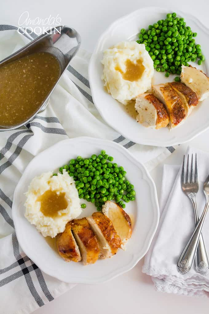 Crockpot Chicken on a plate with peas, potatoes, and gravy
