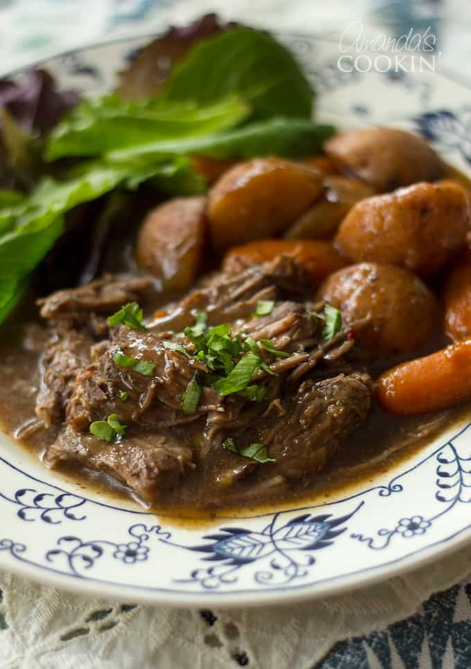 crockpot roast beef with carrots and salad on a plate