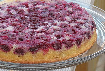 A close up photo of a raspberry upside down cake on a clear cake stand.