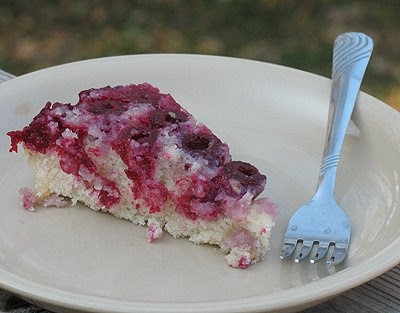 A close up photo of a slice of raspberry upside down cake on white plate served with a fork.