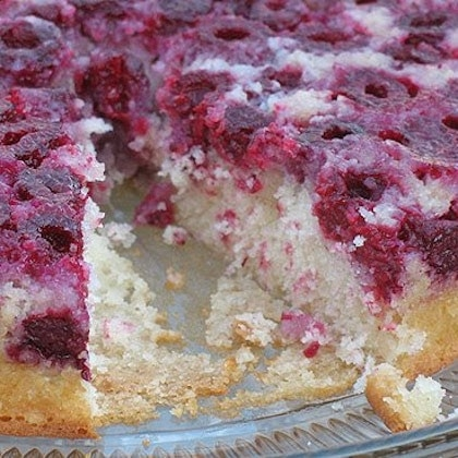 A close up photo of a raspberry upside down cake on a clear platter with a slice missing.