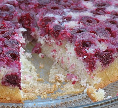 A close up photo of a raspberry upside down cake on a clear cake stand with a slice missing.