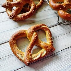 A close up overhead of a homemade German pretzel with more in the background.