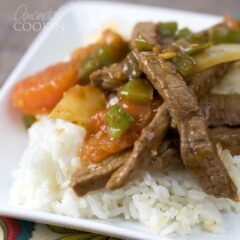 A close up of a white plate with white rice and Chinese pepper steak on top.