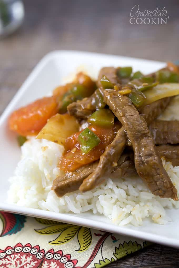 A close up of a white plate with rice and Chinese pepper steak on top.