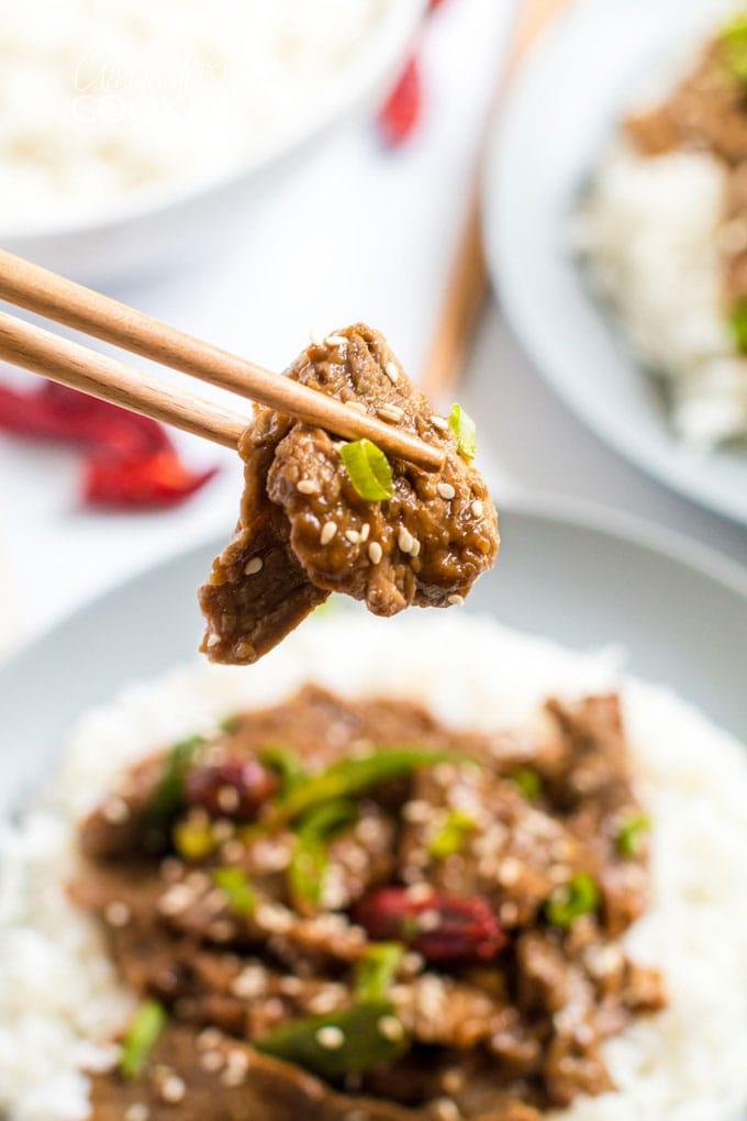 chop sticks holding a piece of mongolian beef