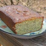 Orange poppy seed pound cake loaf on a decorative plate.