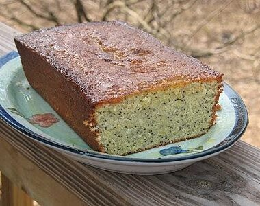 Orange poppy seed pound cake loaf on a decorative plate.