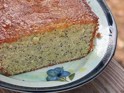 A close up photo of an orange poppy seed pound cake loaf on a decorative plate.