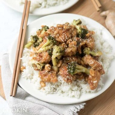 Sesame chicken is complemented by a mixture of diced ginger, red wine vinegar, hoisin sauce, soy sauce, and topped with broccoli and sesame seeds and an optional addition of peanuts.