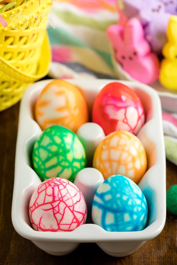 cracked colored eggs in a ceramic egg holder