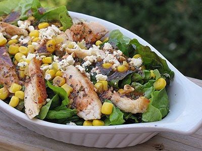 A close up photo of a grilled chicken salad with herbed tomato vinaigrette in a white dish.