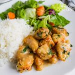 garlic chicken with rice and salad on a plate