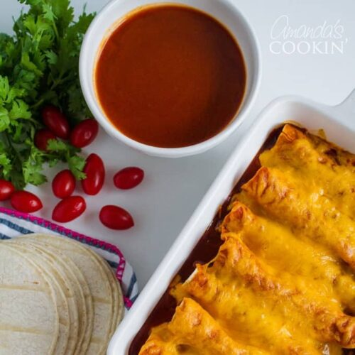 enchiladas in a pan and bowl of emchilada sauce