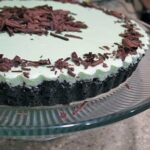 A close up photo of a grasshopper pie on a clear cake stand.