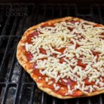 A close up of a pizza on a grill