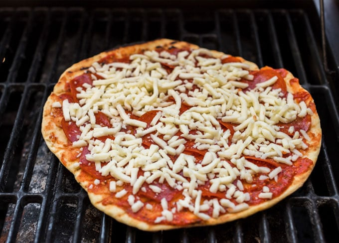 pizza cooking on a gas grill