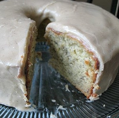 A close up photo of a bananas and cream Bundt cake with brown butter glaze with a slice removed.