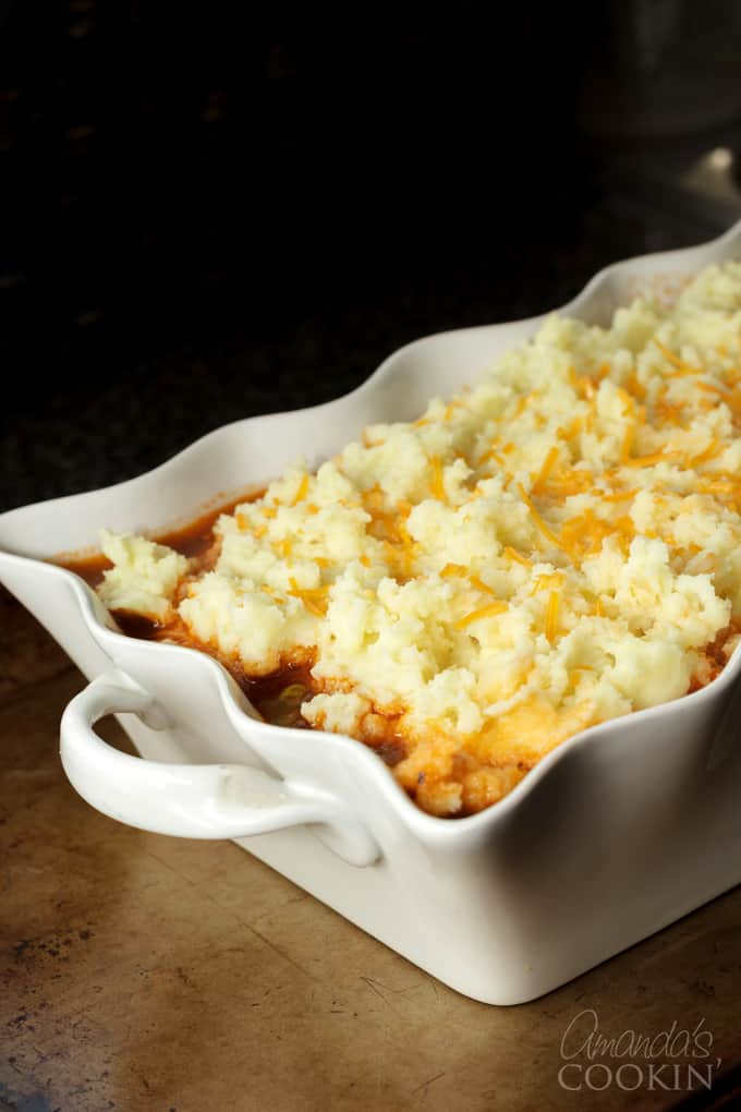 Spoon mashed potato on top of beef. Sprinkle with grated Parmesan cheese and cheddar cheese.