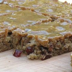 A close up photo of applesauce spice bars resting on a wooden cutting board.