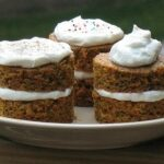 A close up photo of three carrot cake towers topped with fluffy cream cheese frosting.