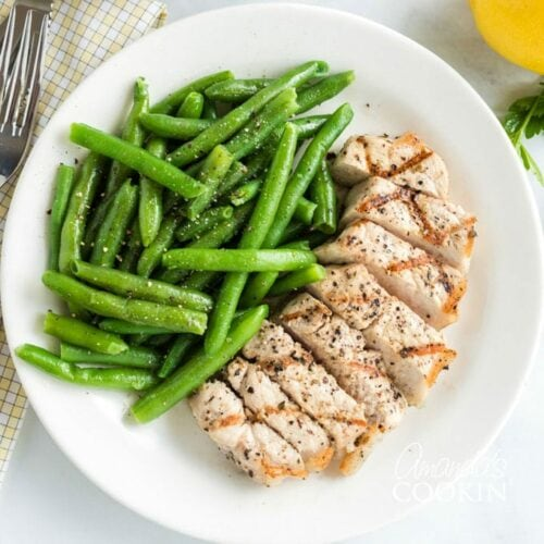 A plate of food with pork chops and green beans