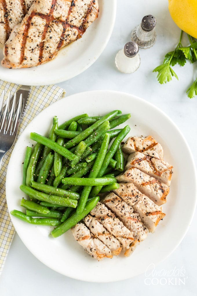 sliced pork chop on a plate with green beans