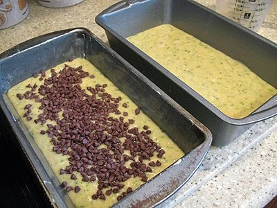 A photo of two loaf pans filled with morning glory zucchini bread batter.