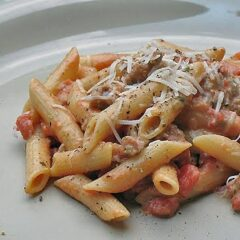 A close up of Penne with tomato sage sausage sauce on a white plate topped with shredded Parmesan cheese.