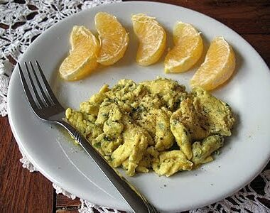 A close up photo of scrambled eggs with garlic, basil and feta with mandarin orange slices to to side on a white plate.