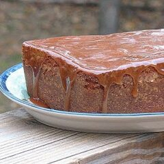 A close up photo of apple cider pound cake with caramel glaze resting on a plate.