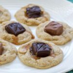 A close up photo of candy bar cookies resting on a white plate.
