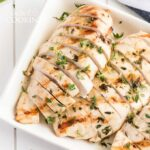 sliced grilled chicken breasts on a platter