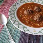 A close up photo of a bowl of Amanda's meatball soup with a spoon resting on the side.