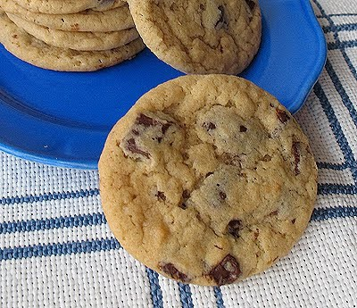 A close up photo of a buttermilk chocolate chip cookie with a plate of cookies in the background.