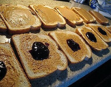 A close up photo of peanut butter spread on slices of bread and a spoonful of jelly on half of the slices.
