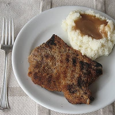 An overhead photo of a grilled breaded pork chop on a white plate with mashed potatoes and gravy and a fork.