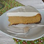 A slice of pumpkin cheesecake with rum whipped topping served on a white plate with a fork.