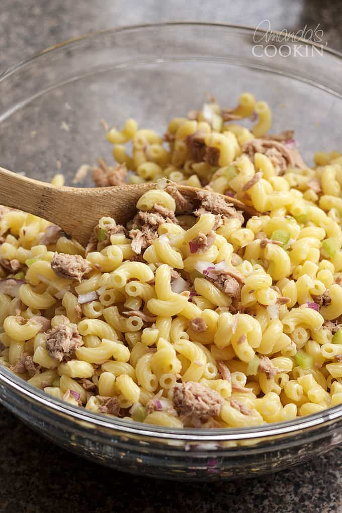 mixing tuna pasta salad ingredients together in bowl