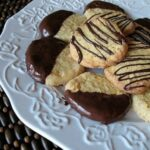A close up photo of toasted coconut orange icebox cookies on a plate.