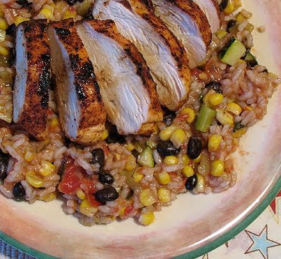An overhead photo of a plate of spicy grilled chicken with baja black beans and rice.