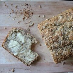 A photo of a loaf of sunflower whole wheat quick bread with a buttered slice to the side all resting on a wooden cutting board.