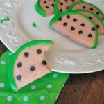 A close up photo of watermelon cookies on a white plate.