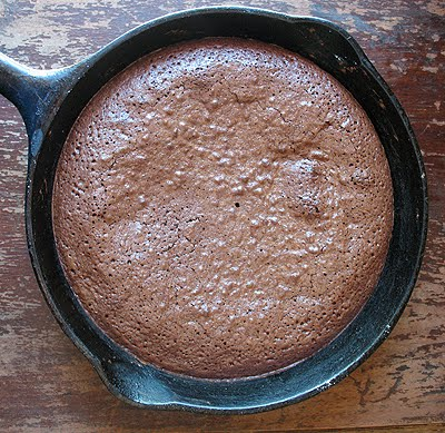 An overhead photo of a cast iron skillet filled with freshly baked brownies.